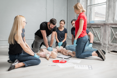 Group of people learning how to make first aid heart compressions with dummies during the training indoors
