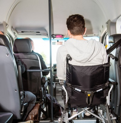 Man in a wheel chair sitting in a modified minivan, used for transporting disabled people